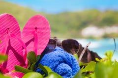桃红色触发器、太阳镜和蓝色毛巾在热带塞舌尔群岛靠岸 海岸线海岛mahe端口塞舌尔群岛 免版税图库摄影