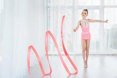 桃红色运动服礼服的美丽的矮小的体操运动员女孩,做节奏体操锻炼成螺旋形与艺术丝带 库存图片