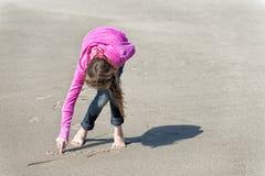 桃红色运动衫的女孩在海滩的沙子画 免版税库存图片