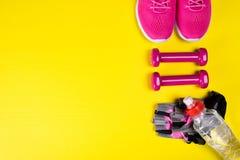 桃红色运动鞋和辅助部件健身的和一个瓶水,在黄色背景,与一个地方写的 库存图片