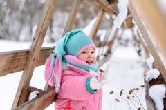 桃红色连衫裤步行的女孩在一个多雪的冬天公园 库存照片