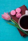 桃红色郁金香、一杯咖啡,书和三个桃红色蛋白杏仁饼干 免版税库存图片