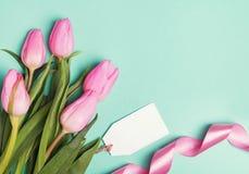 桃红色郁金香、丝带和空的礼物在淡色绿色backgroun标记 库存图片