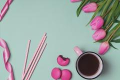 桃红色郁金香、咖啡和其他对象在薄荷的颜色背景 免版税图库摄影