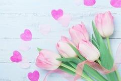 桃红色郁金香为妇女或母亲节开花装饰的心脏和丝带在蓝色桌上 美好的看板卡春天 顶视图 库存图片