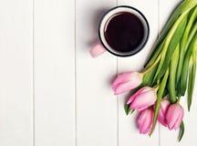 桃红色郁金香和咖啡在一个杯子在白色桌上 库存图片