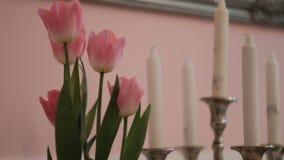 桃红色郁金香和白色蜡烛在桌上在客厅 股票录像