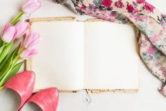 桃红色郁金香和空白的书与妇女` s鞋子在白色木 免版税库存图片