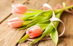 桃红色郁金香春天花束在葡萄酒木头的 库存照片