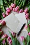 桃红色郁金香框架表面上的 在卡拉服特信封和黑笔里面 免版税库存照片
