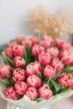 桃红色郁金香美丽的豪华花束在桌上开花 卖花人的工作在花店 库存照片