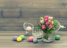 桃红色郁金香花和复活节彩蛋。葡萄酒样式 库存图片