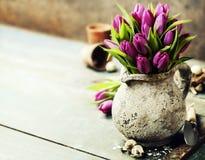 桃红色郁金香花束、复活节彩蛋和园艺工具 库存图片