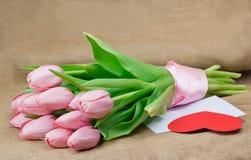 桃红色郁金香花束与缎丝带、信封和心脏的 库存照片