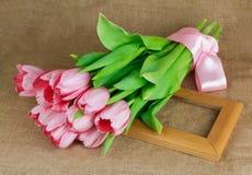 桃红色郁金香花束与说谎在框架的缎丝带的 图库摄影