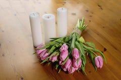 桃红色郁金香花束在美好的木背景的与蜡烛倒带与工艺螺纹 库存图片