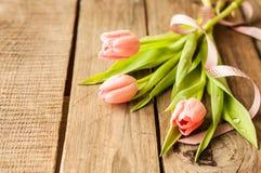 桃红色郁金香花束在葡萄酒木头桌上的 免版税库存照片