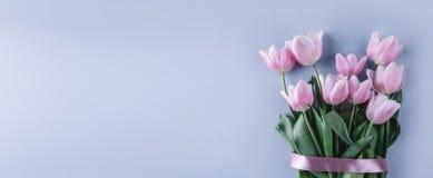 桃红色郁金香花束在蓝色背景开花 等待的春天 免版税库存照片