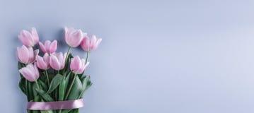 桃红色郁金香花束开花在浅兰的背景 贺卡或婚礼邀请 免版税库存图片