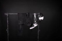 桃红色销售额黄色 黑白运动鞋,盖帽气喘,垂悬在衣裳的牛仔裤折磨背景 星期五 复制空间 库存照片