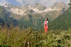 桃红色长的礼服的少妇在多雪的山背景 免版税库存照片