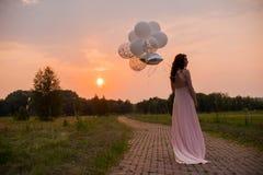 桃红色长的礼服的愉快的美丽的妇女走与气球的在绿色公园日出夏日 库存图片