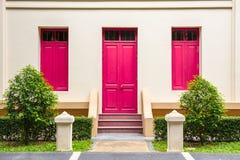 桃红色门,在奶油色墙壁上的桃红色窗口在与sma的桃红色楼梯 免版税图库摄影