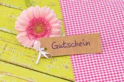 桃红色雏菊花和礼物用德国词Gutschein,手段证件或者优惠券标记为母亲或情人节 免版税库存图片