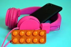 桃红色顶上的外在大耳机、黑电话有一台双重照相机的和指纹传感器,片剂在橙色包装 免版税库存图片