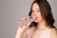 桃红色顶面饮用水的夫人 关闭 灰色背景 图库摄影