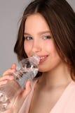 桃红色顶面饮用水的女孩 关闭 灰色背景 免版税图库摄影