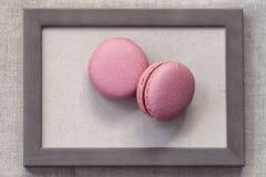 桃红色颜色两个fresch蛋白杏仁饼干在木制框架,抽象甜艺术的 图库摄影