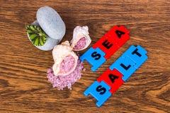 桃红色颜色海盐在壳、题字和两块石头lyi的 免版税库存照片