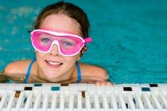 桃红色风镜面具的逗人喜爱的愉快的女孩在游泳池 库存图片