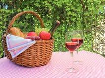 桃红色餐巾野餐篮子和两杯酒 免版税库存照片