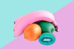 桃红色香蕉,蓝色猕猴桃和红色柠檬静物画,在桃红色和蓝色背景 平的位置 免版税图库摄影