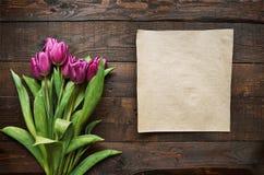桃红色,在黑暗的谷仓木板条背景的郁金香束 库存照片