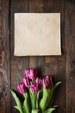 桃红色,在黑暗的谷仓木板条背景的郁金香束 免版税库存照片