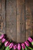 桃红色,在黑暗的谷仓木板条背景的郁金香束 免版税图库摄影