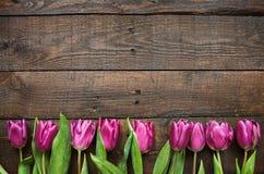 桃红色,在黑暗的谷仓木头板条的郁金香束 库存照片