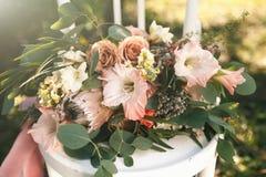 桃红色,白色和珊瑚花和绿叶嫩婚礼花束在太阳点燃的一把白色葡萄酒椅子说谎 库存图片