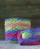 桃红色,紫罗兰色,洋红色,白色和绿色袋子和毛线球 编织的,钩针编织棉纱品 明亮的袋子起点  免版税图库摄影