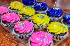 桃红色,黄色和紫色杯形蛋糕准备好党 免版税库存照片