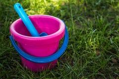 桃红色婴孩桶和蓝色铁锹 库存图片