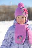 桃红色围巾和帽子的微笑的小女孩看  库存图片