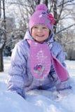 桃红色围巾和帽子的愉快的小女孩在雪爬行 库存照片