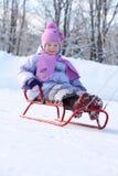 桃红色围巾和帽子的愉快的小女孩去tobogganing 免版税图库摄影