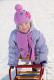 桃红色围巾和帽子的温暖地加工好的微笑的女孩依靠雪撬 免版税库存图片