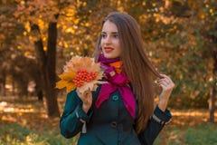 桃红色围巾的可爱的女孩在拿着叶子和花揪的肩膀看  免版税库存照片