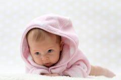 桃红色浴巾的逗人喜爱的矮小的女婴 免版税图库摄影